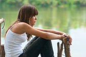 Pretty teenage girl sitting on the dock beside the river on beautiful summer day — Stock Photo