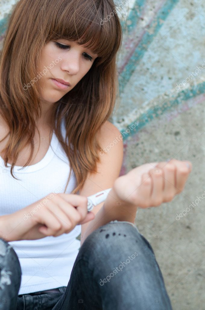 Pretty depressed teenage girl preparing to cut her wrists open  Stock Photo #11968932