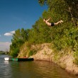 Young man jumping from the shore into the river on sunny summer day — Stock Photo