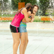 Stock Photo: Teenage girls having fun in towns water fountain on hot summer day