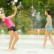 Teenage girls having fun in the towns water fountain on hot summer day — Stock Photo