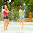 Stock Photo: Teenage girls having fun in the towns water fountain on hot summer day