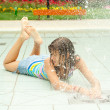 Teenage girl having fun in the water fountain on hot summer day — Stock Photo