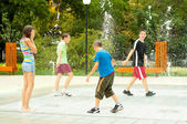 Teenage boys and girls having fun in the towns water fountain on hot summer day — Stock Photo
