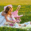 Cute little girl playing with her baby toy on the meadow on sunny summer day — Stock Photo