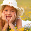 Cute little girl lying on the meadow on sunny summer day - 
