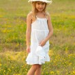 Cute little girl standing on the meadow on sunny summer day - 