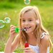Cute little girl blowing soap bubbles on the meadow on sunny summer day - 