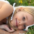 Cute smiling little girl lying on the blanket on the meadow on beautiful summer day - 