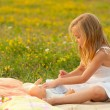 Cute little girl playing with her baby toy on the meadow - 