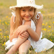 Cute little girl sitting on the meadow on sunny summer day - 