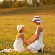 Mother and daughter having fun on the meadow on sunny summer day - 