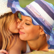 Cute little daughter kissing her mother in the cheek on sunny summer day - 