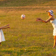 Mother and daughter throwing ball to each other on the meadow on sunny summer day - 