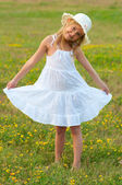 Cute little girl in white dress and hat walking on the meadow on sunny summer day — Stock Photo