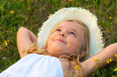 Cute little girl lying on the meadow and daydreaming on beautiful summer day — Stock Photo