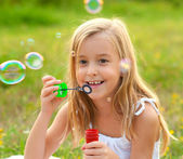 Cute little girl blowing soap bubbles on the meadow on sunny summer day — Stock Photo