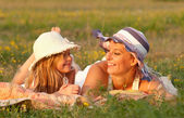 Mother and daughter lying on the meadow on sunny summer day — Foto de Stock