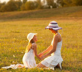 Mother and daughter having fun on the meadow on sunny summer day — Stock Photo