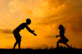 Silhouettes of mother and daughter meeting on the meadow at summer sunset — Stock Photo