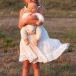 Sad little girl standing alone and holding her baby toy on sunny summer day — Stock Photo
