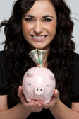 Woman Putting holding Piggy Bank — Stock Photo