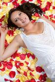 Beautiful Woman in Rose Petals — Stock Photo