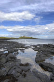 Dunstanburgh Castle and shoreline — Stock Photo