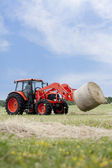 Tractor Hauling Round Bale — Stock Photo