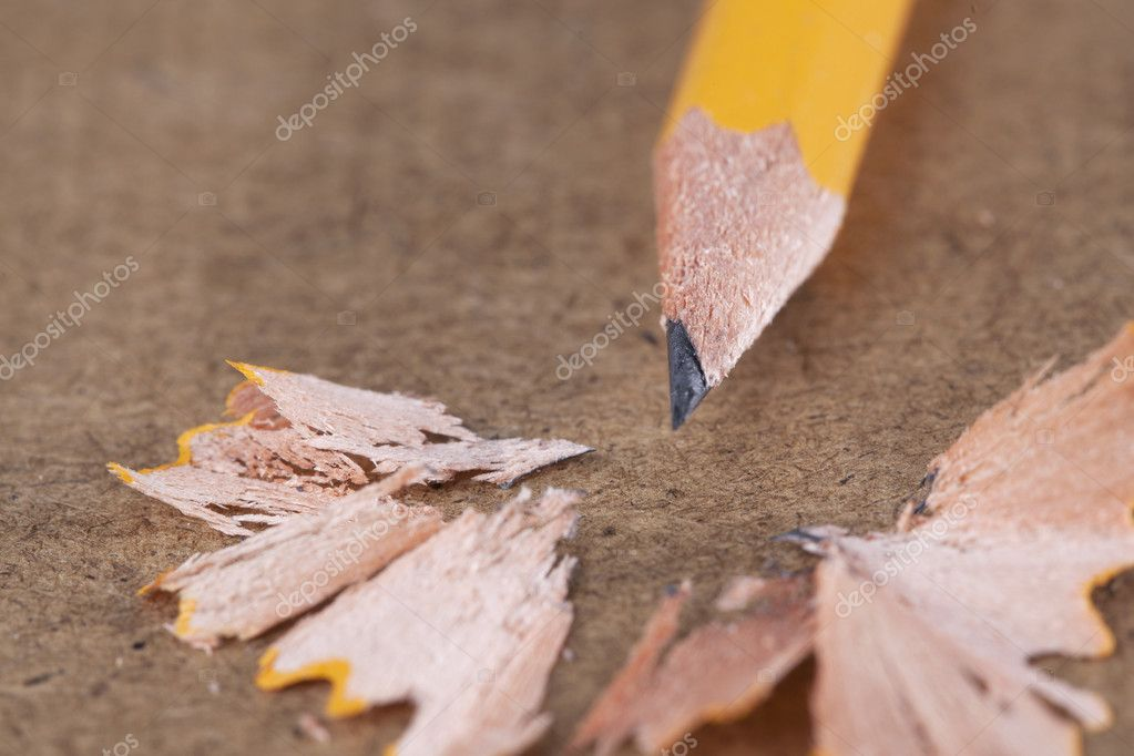 A yellow pencil sits on a wooden desktop with pencil shavings surrounding it. — Stock Photo #12326308