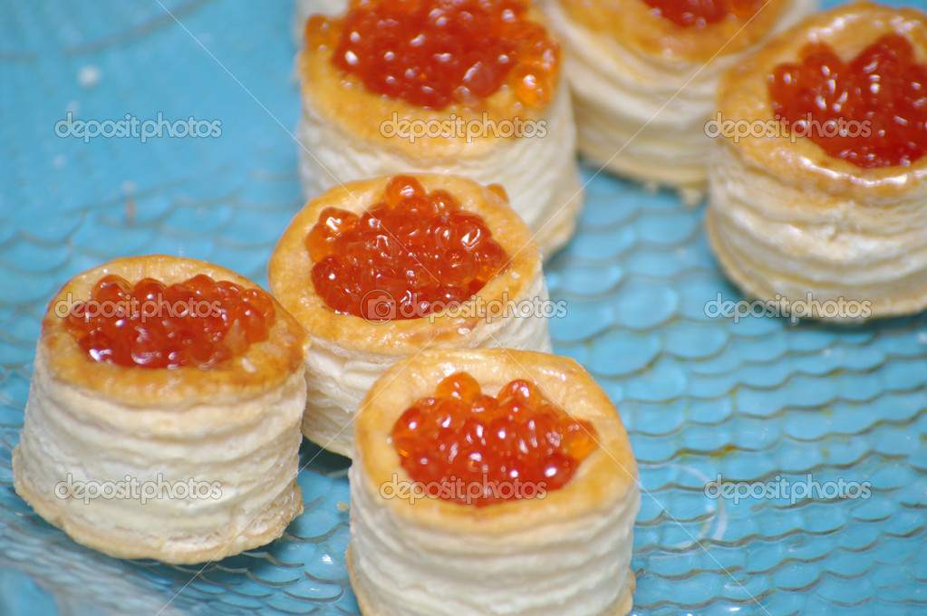 Tartlets with red caviar on blue background  Stock Photo #11404345