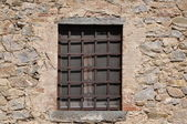 Steel grid and window in stone wall — Stock Photo