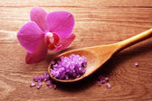 Bath salt in a spoon and flowers of orchids — Stock Photo