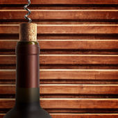 Corkscrew and bottle of wine on the board — Stock Photo