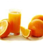 Glass of orange juice and oranges — Stock Photo