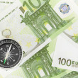 Many euro bank notes and a compass lie side by side - Stock Photo