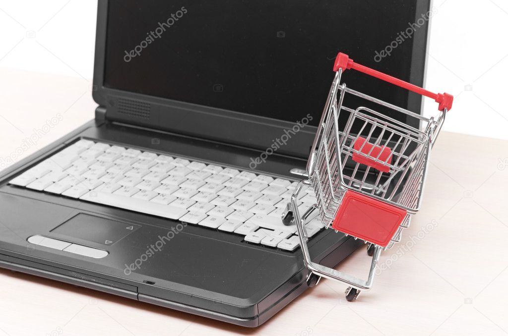 Online shopping. trolley on laptop isolated on white — Stock Photo #10948208