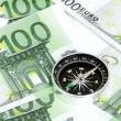 Many euro bank notes and a compass lie side by side — Stock Photo #11195013