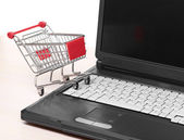 Online shopping. trolley on laptop isolated on white — Stock Photo