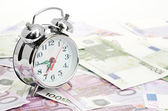 Alarm clock for euro banknotes isolated on white — Stock Photo