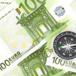 Many euro bank notes and a compass lie side by side — Stock Photo #11390681