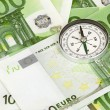 Many euro bank notes and a compass — Stock Photo