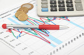 Calculator, coins and pen laying on chart — Stock Photo