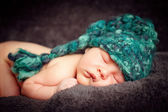 Newborn baby (at the age of 7 days) in a knitted striped hat — Stockfoto