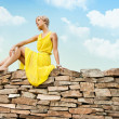 Royalty-Free Stock Photo: The girl is sitting on a stone wall