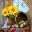 Stock Photo: Vase with sunflowers and by basket with apples