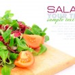 Fresh mixed salad with tomatoes on a wooden board — Stock Photo