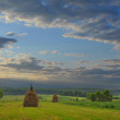 Beautiful sky is after sunset of a sun and summer meadow with haycocks — Foto Stock