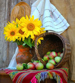 Vase with sunflowers and by a basket with apples — Stockfoto