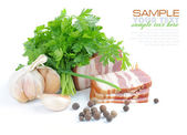 Pieces of bacon are with the bunch of green parsley and garlic on a white background — Stock Photo